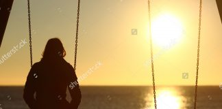 stock photo lonely woman watching sunset alone in winter on the beach at sunset