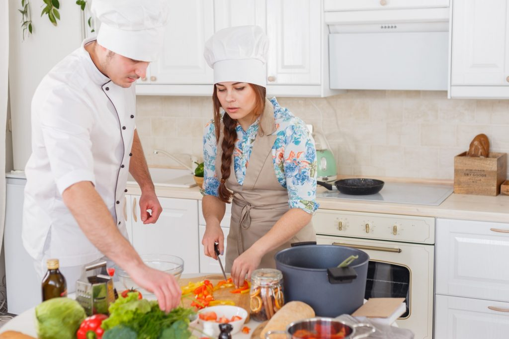 A senior chef giving cooking lesson to young chefs