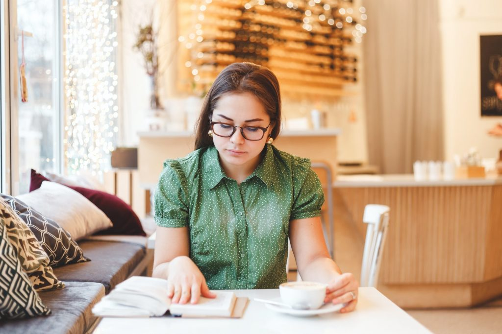 Beautiful young woman relaxing and reading a book in coffee shop