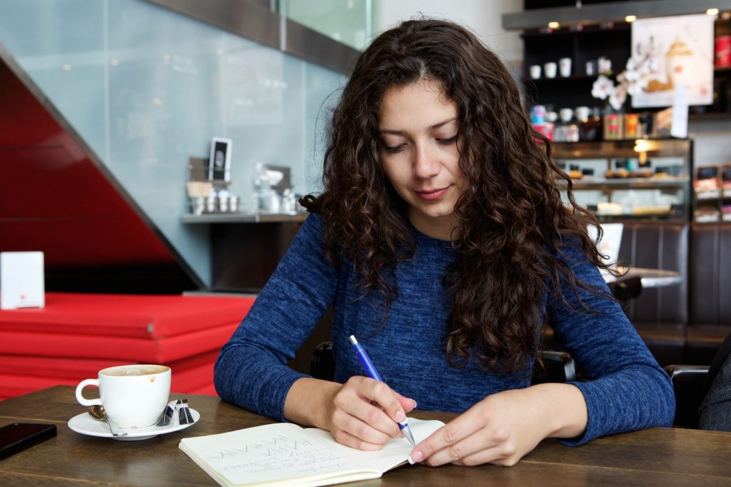 Young woman sitting at coffee shop table and writing a book