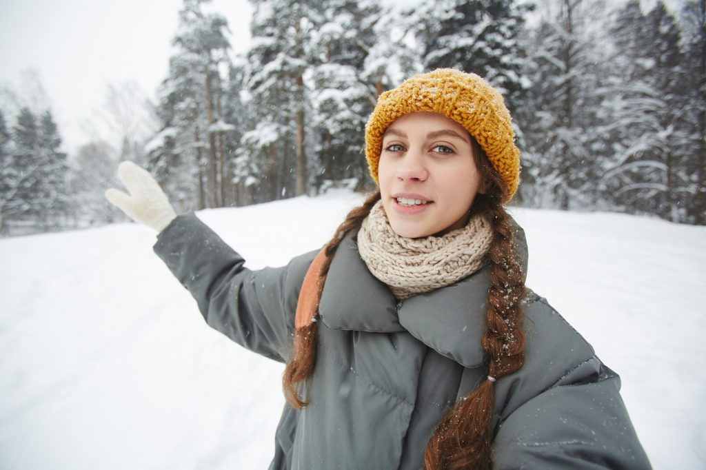 Young female travel blogger giving tour in winter forest