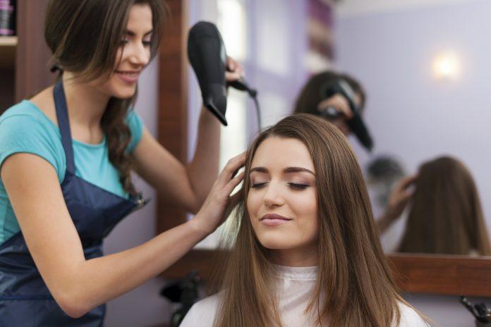 Hair stylist drying woman's hair