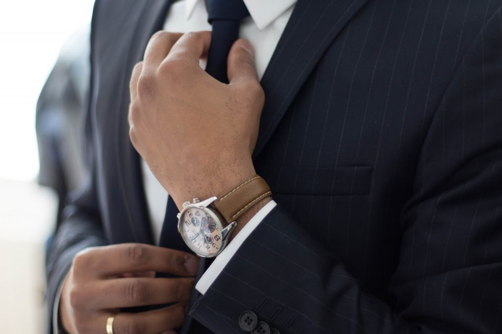 Man in suit with watch adjusting cufflinks.