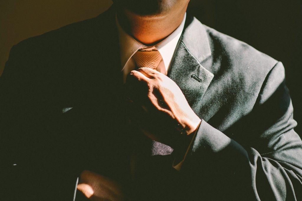 Adjusting necktie in suit, building confidence.