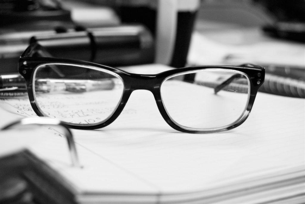 black framed glasses on paper exam