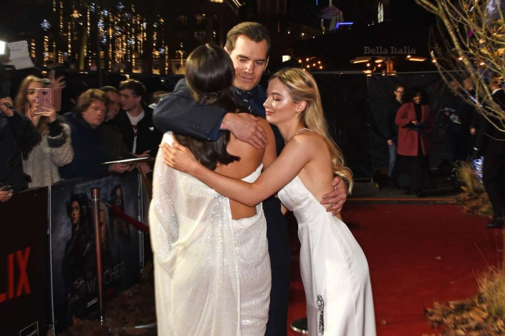 Freya Allen, Henry Cavill and Anya Chalotra embracing