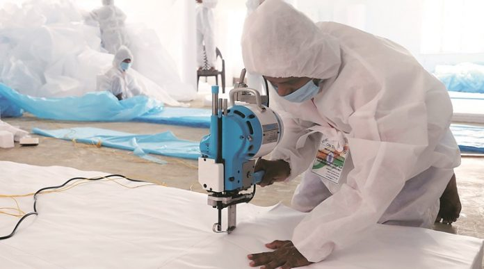 Manufacturing of PPE kit by worker.