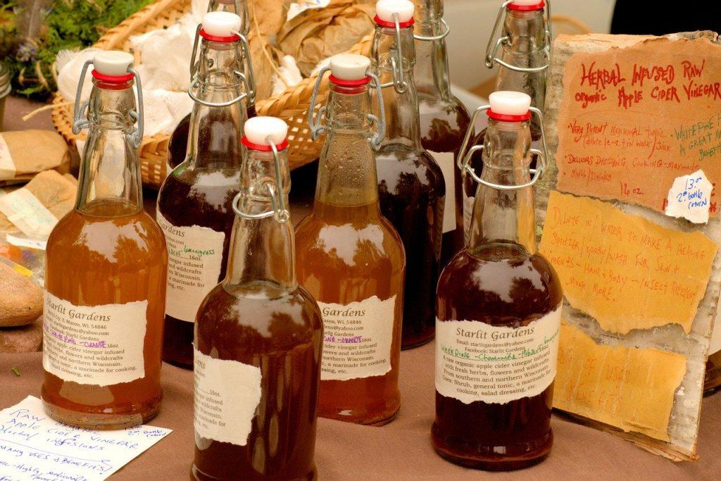 apples cider vinegar in different glass bottles