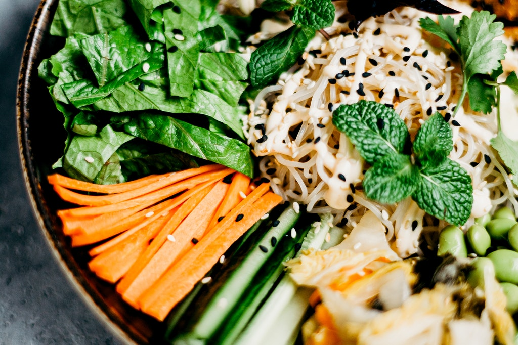 a bowl of raw vegetable with sprouts