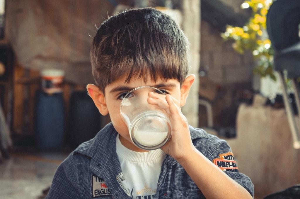 a boy gulping a glass of milk