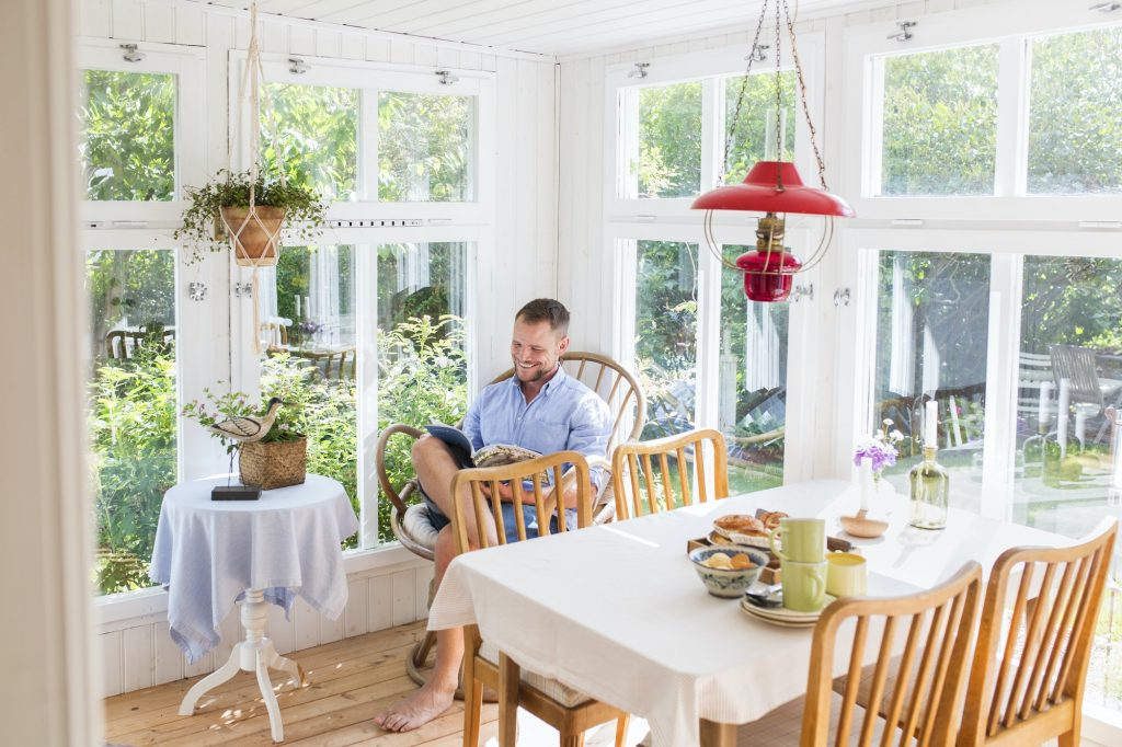 Man reading newspaper in dining room