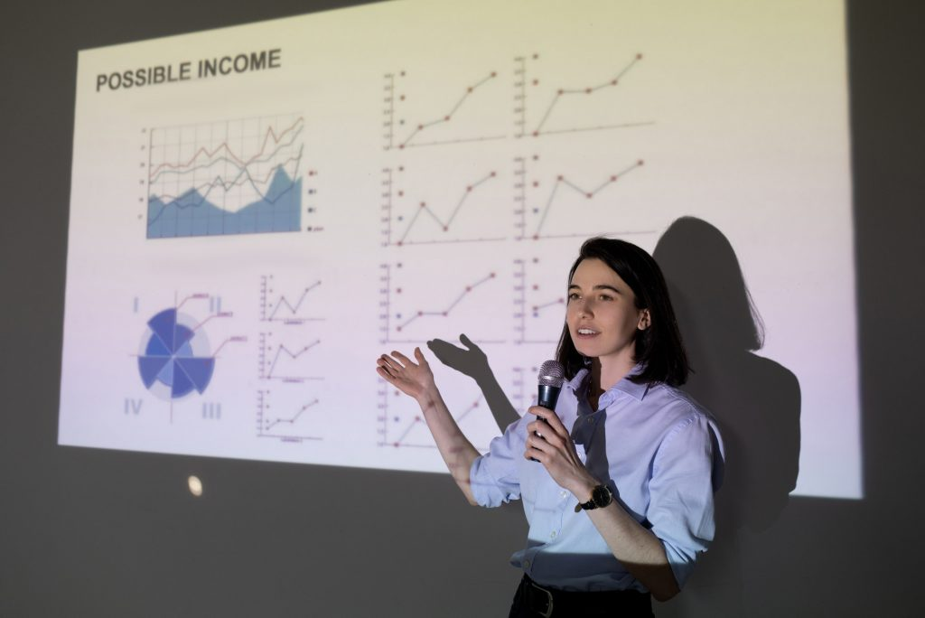 Young confident female marketer showing graph of financial development