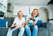 Child son and mother playing video games together at home