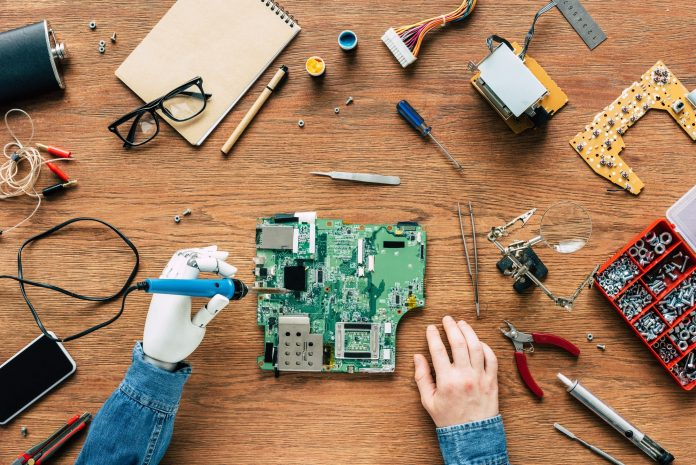 cropped image of electronic engineer with robotic hand fixing motherboard by soldering iron at table