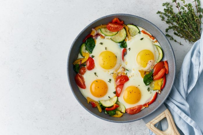 Fried eggs poached with vegetables on teflon pan, Keto meal, FODMAP recipe